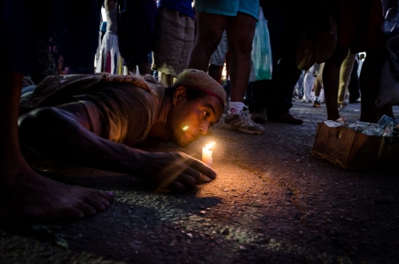 candles and pilgrims in a travel of photography in honour of saint lazarus in cuba