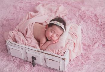 niña recien nacida en cajon blanco y fondo rosa