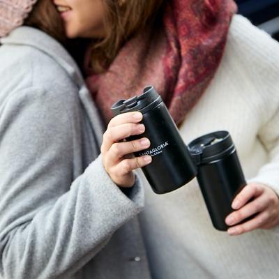 Dos amigas se dan un abrazo mientras sostienen un vaso Take Away de las pastelerías Santa Gloria