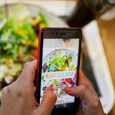 Detalle de unas manos que sujetan un móvil mientras sube una fotografía a Instagram con el hashtag Santa Gloria