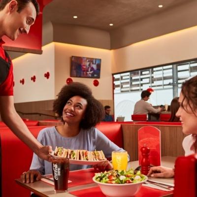 Fotografía de un camarero de VIPS sirviendo una bandeja a una mesa con dos chicas.
