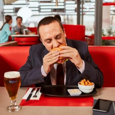 Fotografía de un ejecutivo comiendo una ha,mburguesa en un restaurante VIPS