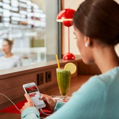 Fotografía publicitaria de una chica mirando el móvil en un restaurante VIPS