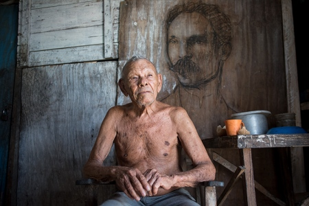 old cuban man with a graffiti of jose marti behind him
