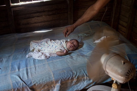 little baby in a bed in front of a fan , anthropological photo of cuba