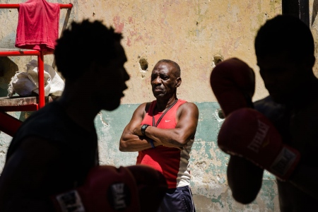 coach of a cuban boxing gym paying attention to his pupils.
