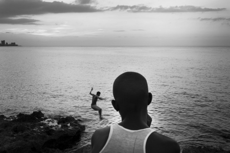 jumping to caribbean sea in Havana, Cuba. Photo essays about travels to Cuba