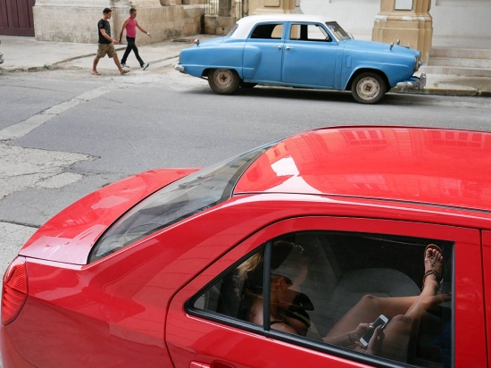 cuban girl inside a car connected to wifi area