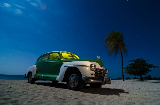 old cars at night in cuba by louis alarcon