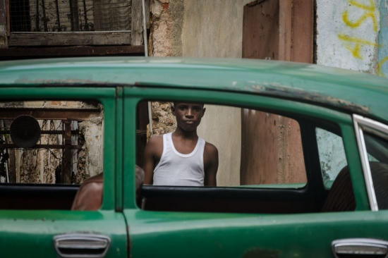 young cuban boy in a car window,  street photography in cuba