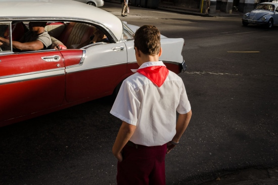 cuban student and old car in havana´s street,  street photography in cuba