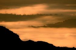 Un montañero disfruta de un dorado amanecer.